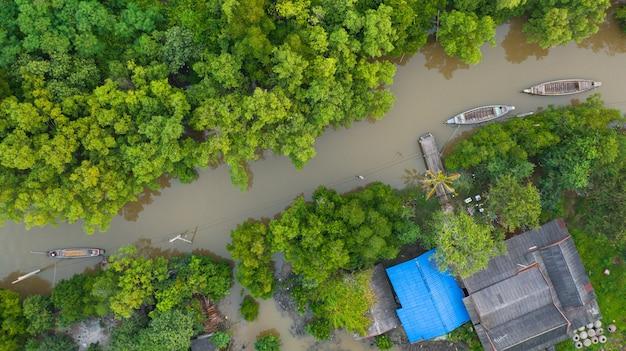 Vue aérienne du bateau de pêcheur dans la campagne thaïlandaise, tir cinématique d'en haut de la vie locale idyllique en thaïlande