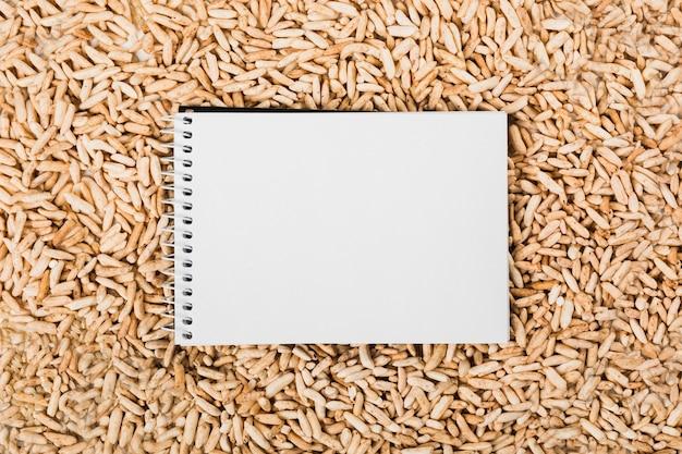 Vue aérienne du bloc-notes blanc en spirale sur le riz brun feuilleté