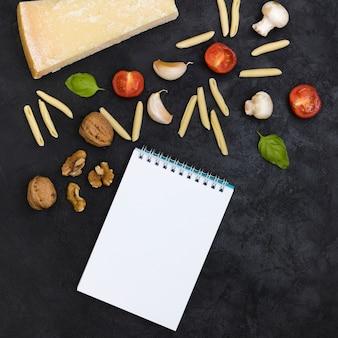 Vue aérienne du bloc-notes à spirale avec les ingrédients nécessaires à la fabrication des pâtes garganelli sur un fond texturé noir