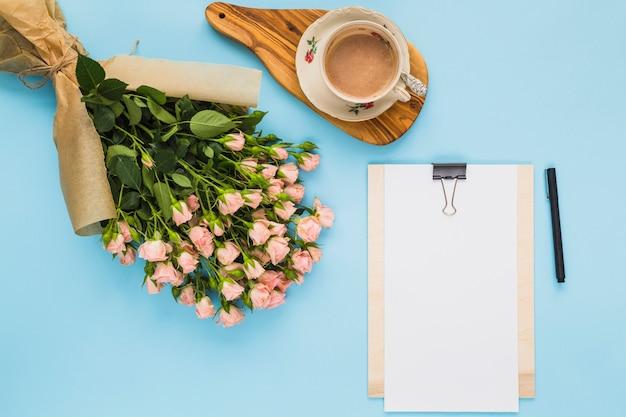 Une vue aérienne du bouquet de fleurs; tasse à café; presse-papier et stylo sur fond bleu