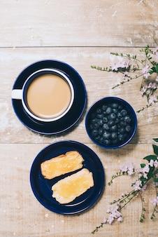 Une vue aérienne du café; myrtilles; pain grillé et fleurs sur un bureau en bois