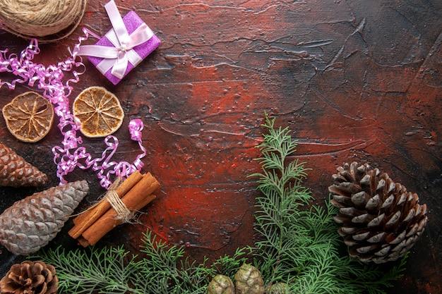 Vue aérienne du cahier fermé avec stylo limes cannelle et une boule de cônes de conifères cadeau corde sur le côté droit sur fond sombre
