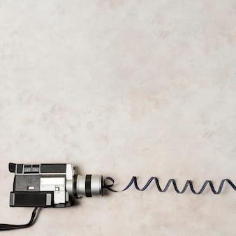 Vue aérienne du caméscope avec des bandes de film tourbillonnantes sur un fond de béton gris