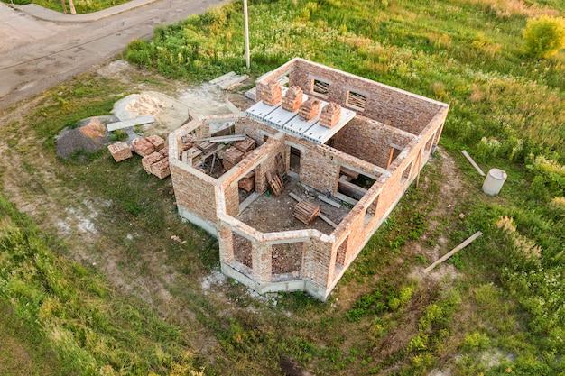 Vue aérienne du chantier de construction de la future maison, du sous-sol en brique et des piles de briques pour la construction.