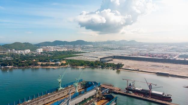 Vue aérienne du chantier naval ont grue machine et porte-conteneurs dans l'océan noir