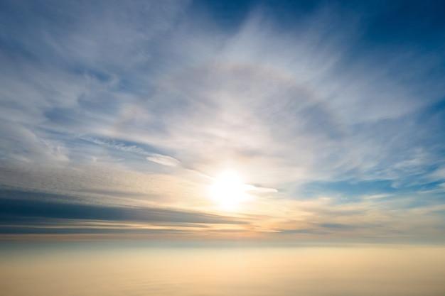 Vue aérienne du coucher de soleil jaune vif sur des nuages denses blancs avec un ciel bleu au-dessus.