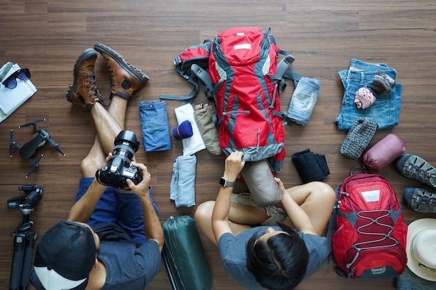 Vue aérienne du couple de jeunes voyageurs effectuant une planification en tenant la caméra