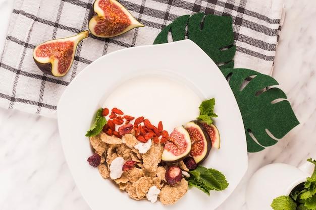 Vue aérienne du délicieux petit déjeuner; fausses feuilles de monstera et torchon de cuisine sur fond de marbre blanc