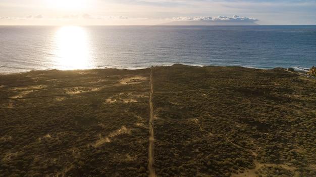 Vue aérienne du drone de l'océan atlantique au coucher du soleil, terrain de buissons et de chemins. horizon au-dessus de l'eau