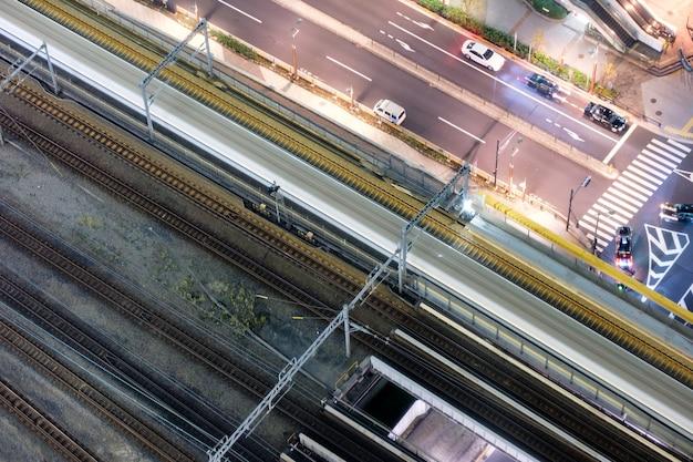 Vue aérienne du flou de mouvement du train à grande vitesse rapide avec le trafic en milieu urbain