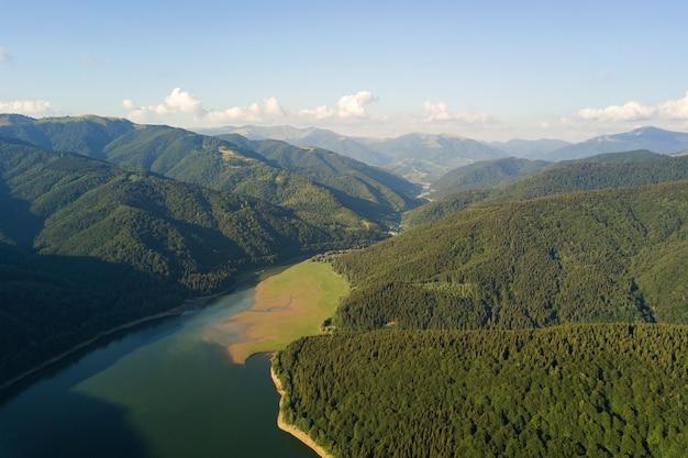 Vue aérienne du grand lac aux eaux bleues claires entre les collines de haute montagne couvertes d'une forêt dense à feuilles persistantes.