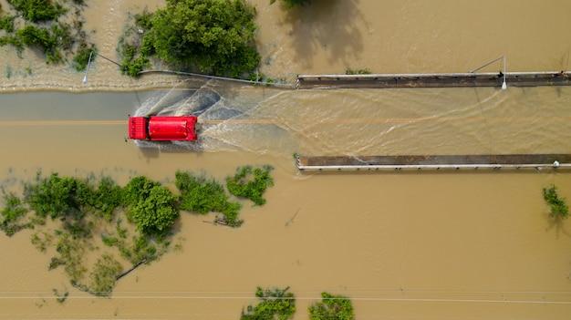 Vue aérienne du haut du village et de la route de campagne inondée avec une voiture rouge, vue d'en haut filmée par drone