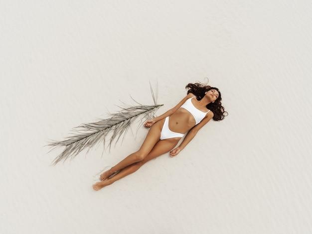 Vue aérienne du haut de la femme en maillot de bain bikini se détendre et bronzer sur la plage