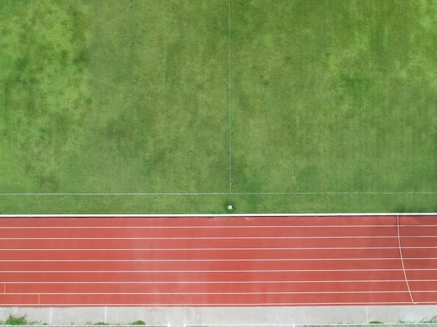 Vue aérienne du haut sur la moitié du terrain de football, terrain de football avec piste de course rouge.