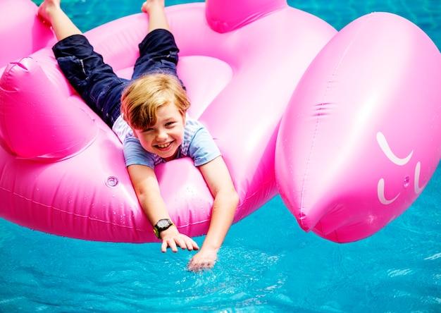 Vue aérienne du jeune garçon caucasien flottant dans la piscine