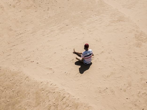 Vue aérienne du jeune hipster assis sur la plage de la mer de sable abstraite. concept exotique d'été d