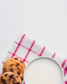 Vue aérienne du lait avec deux biscuits aux pépites de chocolat sur fond blanc