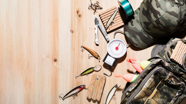 Une vue aérienne du leurre de pêche; pince; flotteur de pêche avec casquette et sac sur le bureau en bois