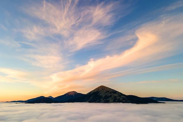 Vue aérienne du lever de soleil jaune vibrant au-dessus des nuages denses blancs un