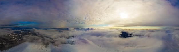 Vue aérienne du magnifique panorama hivernal des pentes enneigées et des collines parmi les nuages blancs luxuriants. le concept de la nature envoûtante de l'hiver rigoureux