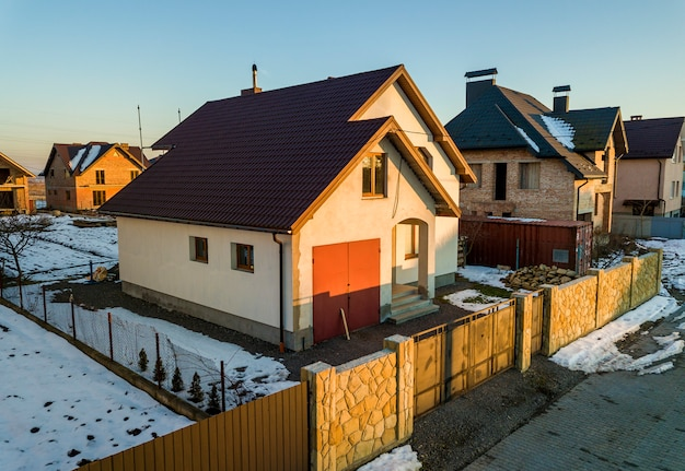 Vue aérienne du nouveau chalet de la maison résidentielle et garage attenant avec toit en bardeaux sur cour clôturée par une journée d'hiver ensoleillée dans une zone de banlieue moderne. investissement parfait dans la maison de rêve.