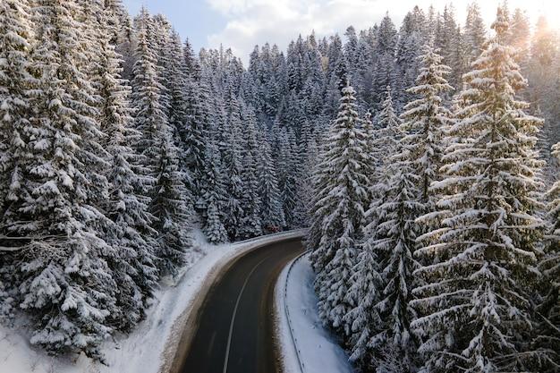 Vue aérienne du paysage hivernal avec des collines de montagne couvertes de neige et une route forestière sinueuse le matin.