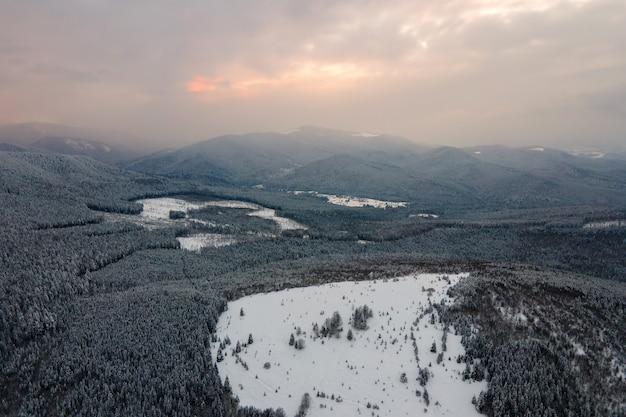 Vue aérienne du paysage hivernal avec des collines montagneuses couvertes de pinède à feuilles persistantes après de fortes chutes de neige par une froide soirée calme.
