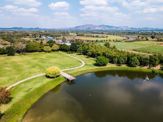 Vue aérienne du paysage de la jetée en bois au lac avec pelouse verte et ciel bleu
