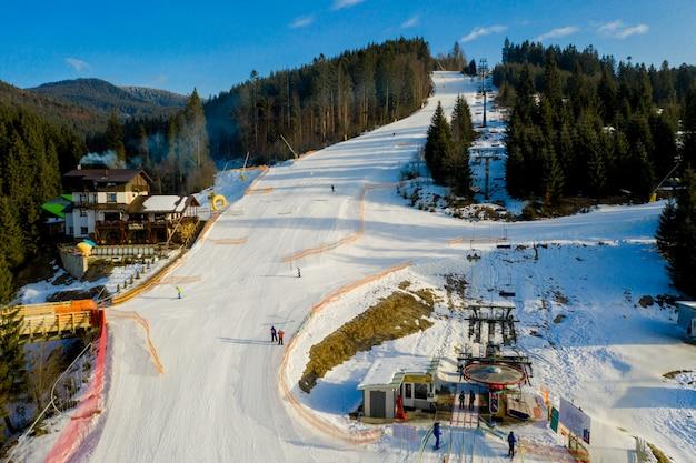 Vue aérienne du paysage des pistes de ski et de snowboard à travers les pins descendant jusqu'à la station d'hiver dans les carpates