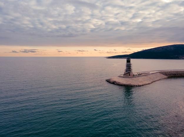 Vue aérienne du phare de la baie de lustica au monténégro à la lumière du coucher du soleil