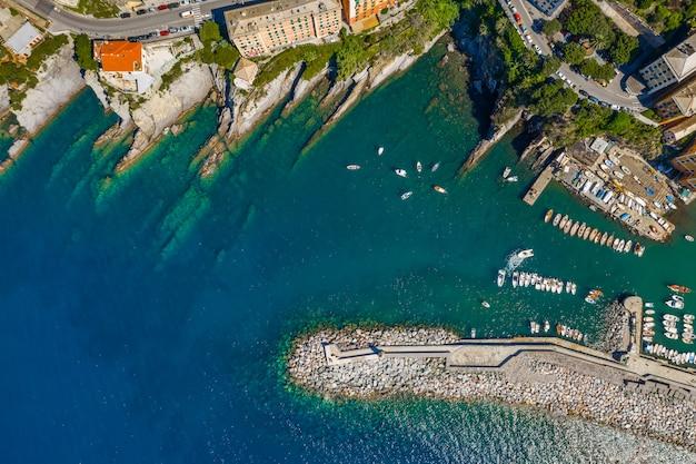 Vue aérienne du port de camogli. bâtiments colorés, bateaux et yachts amarrés dans la marina avec de l'eau verte.