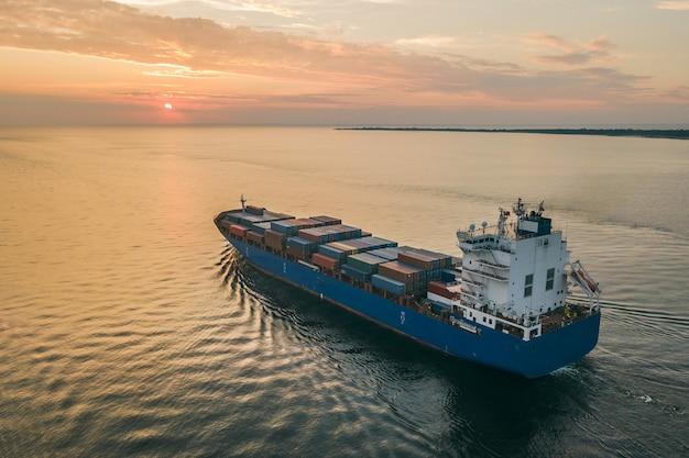 Vue aérienne du porte-conteneurs naviguant en mer au coucher du soleil