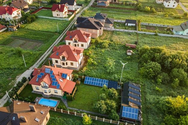Vue aérienne du quartier résidentiel rural avec des maisons privées entre les champs verts au lever du soleil.