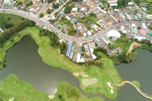 Vue aérienne du quartier vert avec route goudronnée près d'un terrain de golf à phuket, thaïlande.