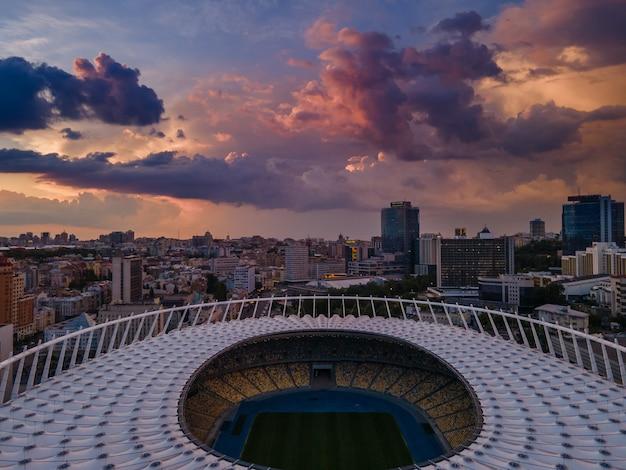 Vue aérienne du stade de football de la ville sur fond de coucher de soleil et de beaux nuages