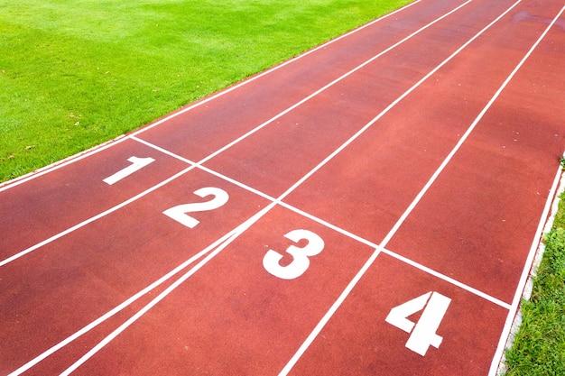 Vue aérienne du stade de sport avec des pistes de course rouges avec des chiffres dessus et un terrain de football en herbe verte.