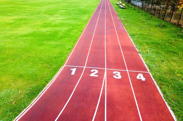 Vue aérienne du stade de sport avec des pistes de course rouges avec des numéros dessus et terrain de football en herbe verte
