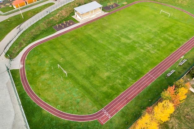 Vue aérienne du stade de sport avec pistes de course rouges et terrain de football en herbe verte.
