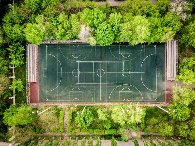Vue aérienne du terrain de basketball entre les arbres de la forêt