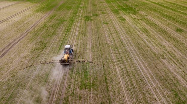 Vue aérienne du tracteur agricole labourant et pulvérisant sur le terrain