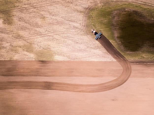 Vue aérienne du tracteur dans le champ, travaux agricoles. tracteur cultivant le champ, vue aérienne