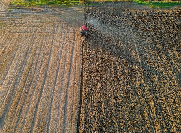 Vue aérienne du tracteur laboure l'automne sur le terrain le soir au coucher du soleil.