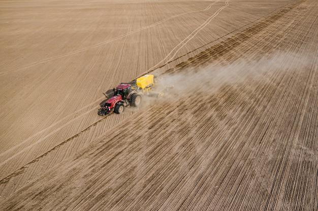 Vue aérienne du tracteur avec semoir monté effectuant l'ensemencement direct des cultures sur un champ agricole labouré. agriculteur utilise des machines agricoles pour le processus de plantation, vue de dessus