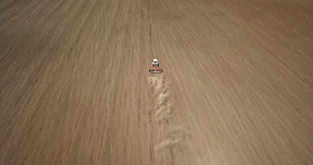 Vue aérienne du travail du tracteur sur le terrain. semer les cultures au printemps.