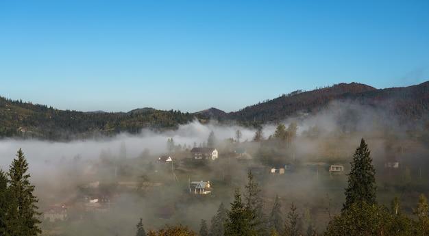 Vue aérienne du village ukrainien brumeux au sommet des montagnes