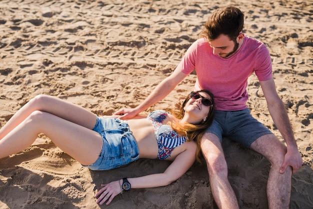 Une vue aérienne de l'élégante jeune femme allongée sur les genoux de son ami garçon assis sur le sable à la plage