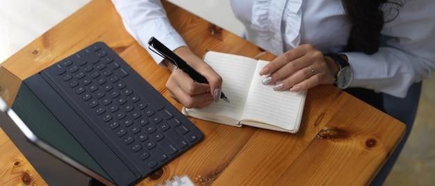 Vue aérienne d'une employée de bureau écrit sur un ordinateur portable vierge tout en travaillant avec une tablette numérique
