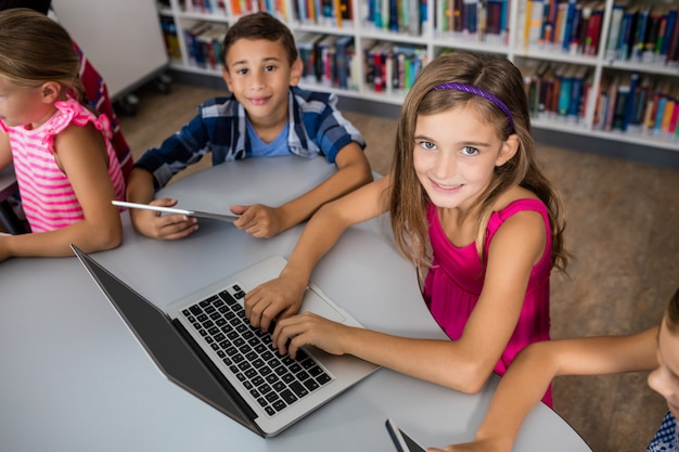 Vue aérienne des enfants à l'aide d'un ordinateur portable et d'une tablette pc