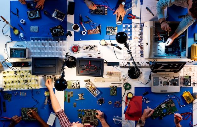 Vue aérienne de l'équipe de techniciens en électronique travaillant sur des pièces d'ordinateur