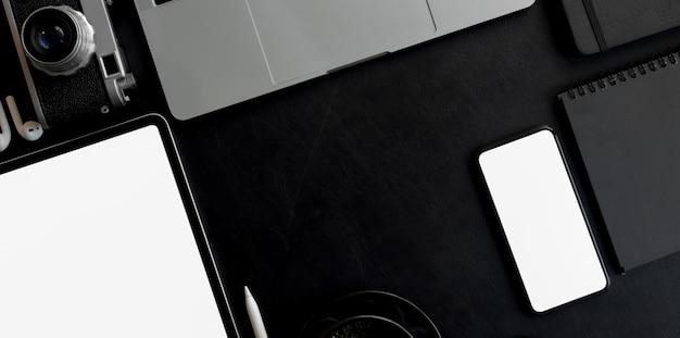 Vue aérienne d'un espace de travail moderne et sombre avec une tablette à écran blanc et un smartphone